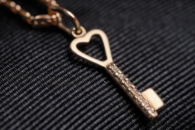 Goldkette mit einem anhänger in form eines schlüssels auf einem schwarzen tuch. Premium Fotos