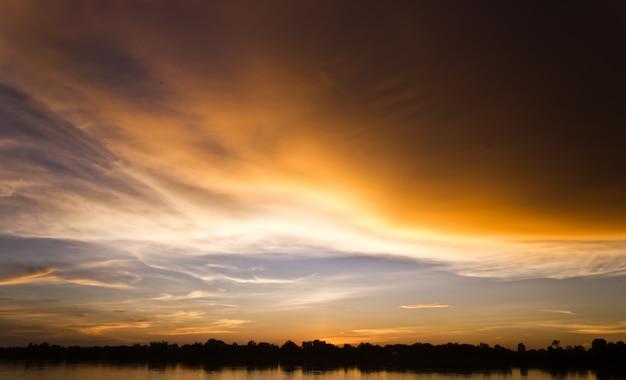 Goldlicht auf der sonne stellte mit licht auf dem fluss ein. idyllisches hintergrundbild sun. Premium Fotos