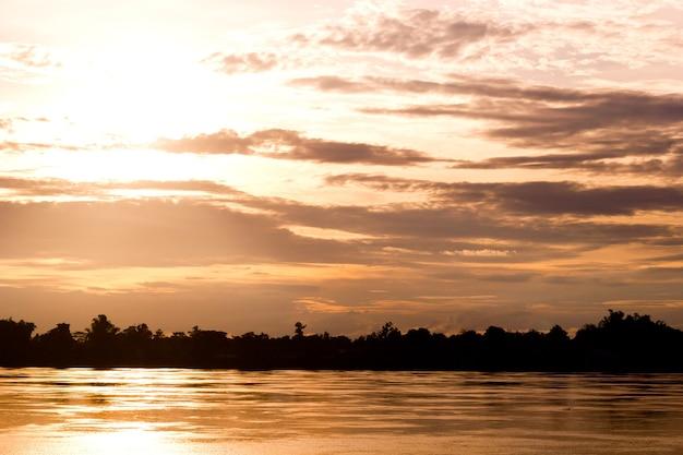 Goldlicht auf sonne stellte mit licht auf dem fluss ein. idyllische tapeten-untergehende sonne. Premium Fotos