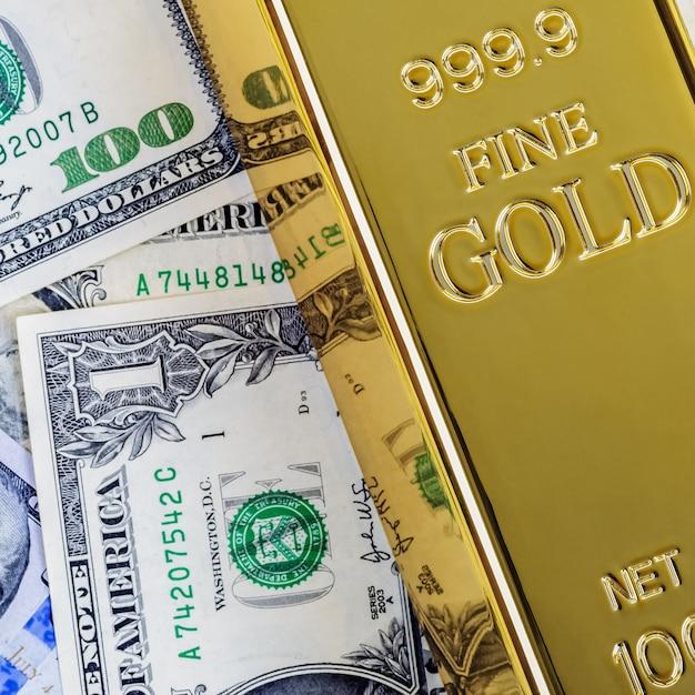 Goldmetallbarrenbarren auf dem hintergrund des dollars und der eurorechnungen. Premium Fotos