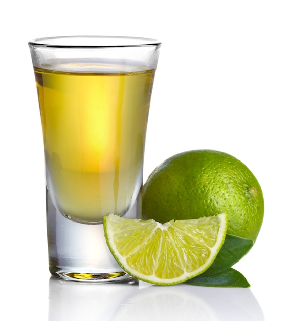 Goldtequila schoss mit dem kalk, der auf weiß lokalisiert wurde Premium Fotos