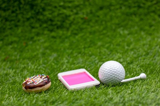 Golfball mit handy auf grünem gras. Premium Fotos