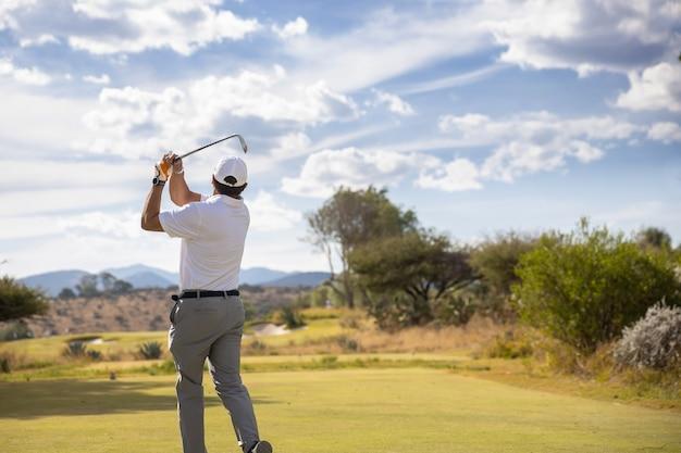 Golfspieler schwingen auf bewölktem himmel Premium Fotos