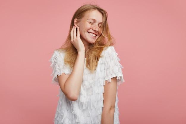 Goog, der junge fröhliche reizende frau mit foxy haaren sieht, die sanft ihr gesicht mit erhobener hand berühren, während sie angenehm mit geschlossenen augen lächeln, lokalisiert über rosa hintergrund Kostenlose Fotos