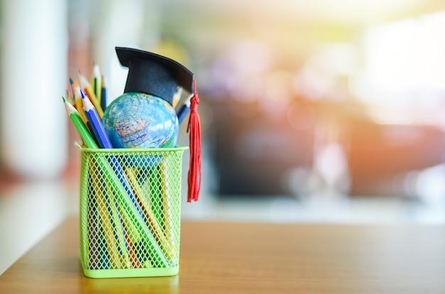 Graduierungshut auf erdkugelmodell globales bildungsstudienkonzept Premium Fotos