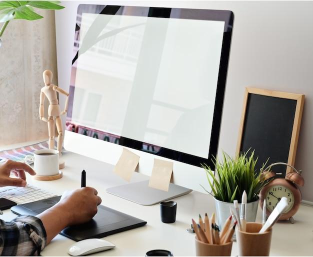 Grafikdesigner, der digitale tablette mit tischrechner im studiobüro verwendet Premium Fotos