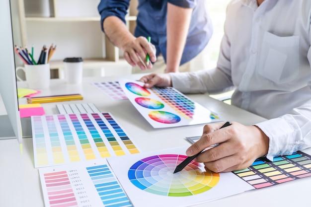 Grafikdesigner mit zwei kollegen, der an farbauswahl und farbmustern arbeitet Premium Fotos