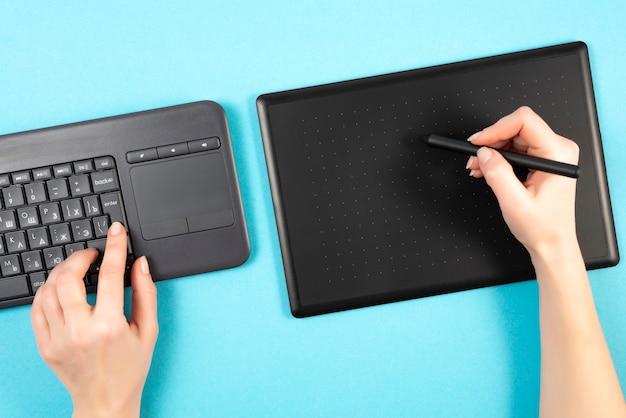 Grafiktablett und tastatur auf einem blauen hintergrund. Premium Fotos