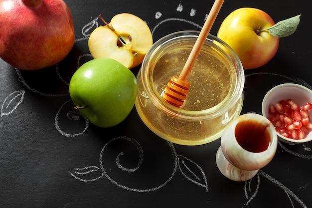 Granatapfel, apfel und honig für traditionelle feiertagssymbole rosh hashanah (jüdischer neujahrsfeiertag) auf schwarzem hintergrund Premium Fotos