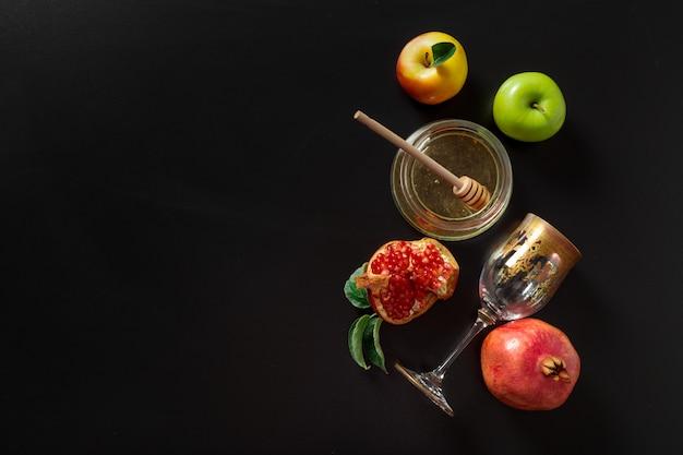 Granatapfel, apfel und honig für traditionelle feiertagssymbole rosh hashanah (jüdischer neujahrsfeiertag) auf schwarzem Premium Fotos