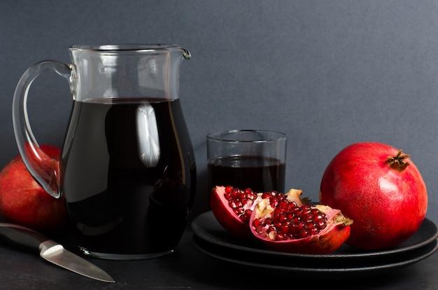 Granatapfel, granatapfelsaft in einer glasschale. dunkler hintergrund. seitenansicht. kopieren sie platz Premium Fotos