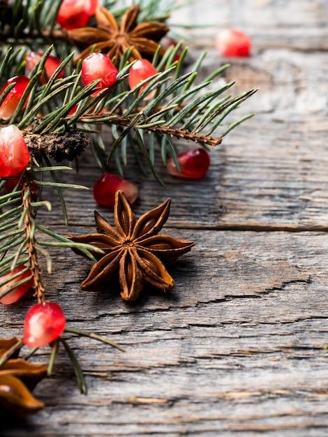 Granatapfelfichte verzweigt sich sternanisnüsse, zimt und wintergewürze auf holz Premium Fotos