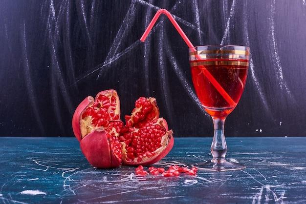 Granatapfelkerne und ein glas saft auf blauem raum. Kostenlose Fotos