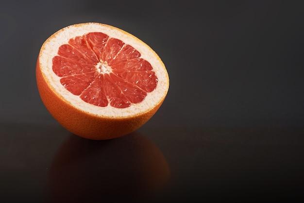 Grapefruit isoliert auf einem schwarzen. saisonales obst Kostenlose Fotos
