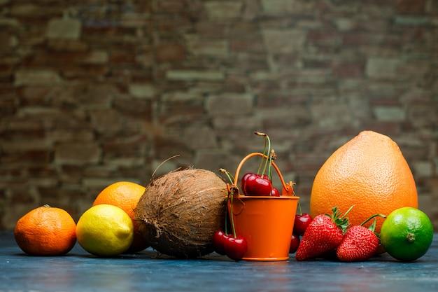 Grapefruit mit orange, limette, zitrone, erdbeere, kirsche, mandarine, kokosnuss-seitenansicht auf ziegelstein und blauem hintergrund Kostenlose Fotos