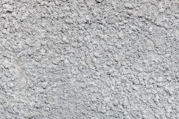 Graue außenwand aus zierputz auf zementbasis. textur der alten mauer. einfarbig. selektiver fokus Premium Fotos