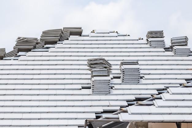 Graue farbe des ziegeldaches im bau mit stapeln auf dach Premium Fotos