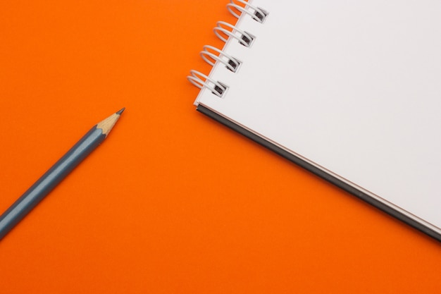 Grauer bleistift auf orange hintergrund, zurück zu schule, bildungskonzept Premium Fotos