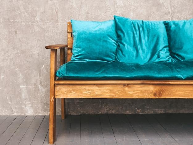 Grauer wandinnenraum mit stilvollem gepolstertem blauem und hölzernem modernem sofa, hängende lampen Kostenlose Fotos