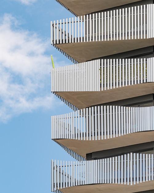 Graues betongebäude mit weißen metallgeländern unter dem blauen himmel Kostenlose Fotos