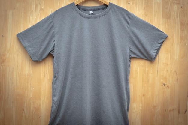 Graues kurzärmliges t-shirt schlichter runder halsspott herauf hölzerne rückseitige bodenvorderansicht der konzeptidee Premium Fotos