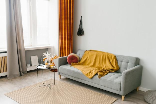 Graues sofa im wohnzimmer im skandinavischen minimalistischen naturstil mit gelber und roter farbe Premium Fotos