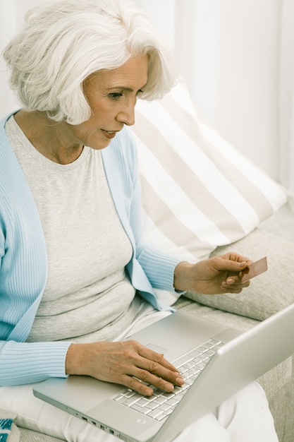 Grauhaarige frau, die laptop für online-einkauf verwendet Premium Fotos