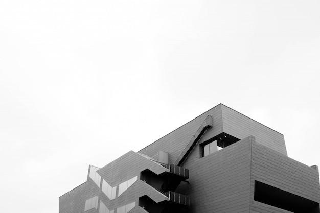 Graustufenaufnahme des niedrigen winkels eines modernen betongebäudes lokalisiert auf einer weißen wand Kostenlose Fotos