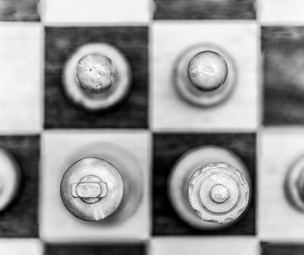 Graustufenaufnahme von schachfiguren auf einem schachbrett Kostenlose Fotos