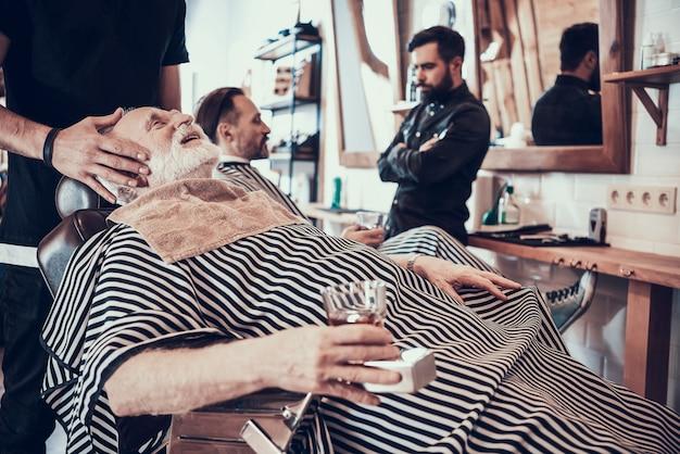 Gray haired man drinks whisky im friseursalon. Premium Fotos