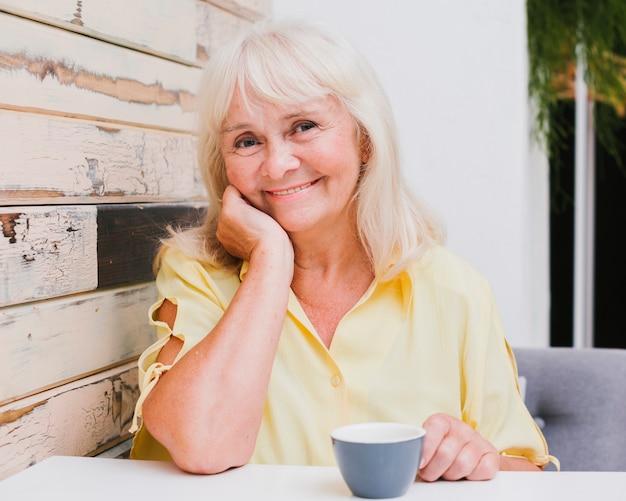 Greisin, die in der küche mit dem schalenlächeln sitzt Kostenlose Fotos