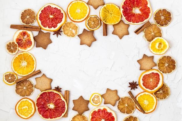 Grenze von getrockneten scheiben des verschiedenen zitrusfruchtlebkuchen- und -gewürzrahmens auf weißer oberfläche mit copyspace Premium Fotos