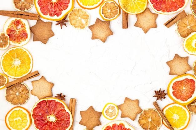 Grenze von getrockneten scheiben des verschiedenen zitrusfruchtlebkuchens und -gewürzen auf weißem hintergrund mit copyspace Premium Fotos