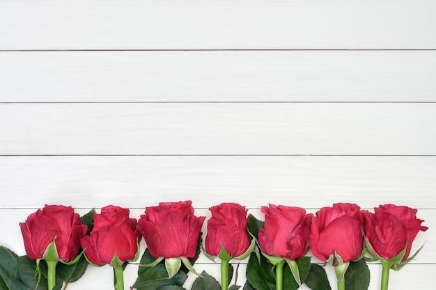 Grenze von roten rosen auf weißem hölzernem hintergrund. draufsicht, exemplar. Premium Fotos
