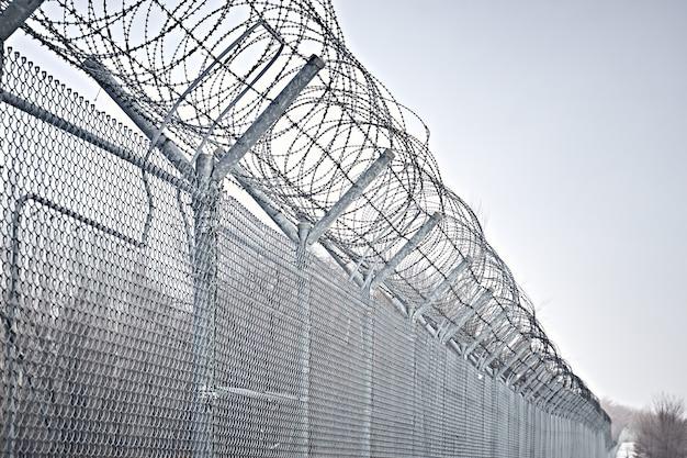 Grenzzaun mit stacheldraht. schließung für quarantäne. haftanstalt für maximale sicherheit. Premium Fotos