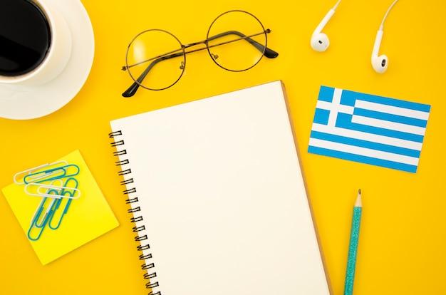 Griechische flagge neben leerem notizbuch Kostenlose Fotos