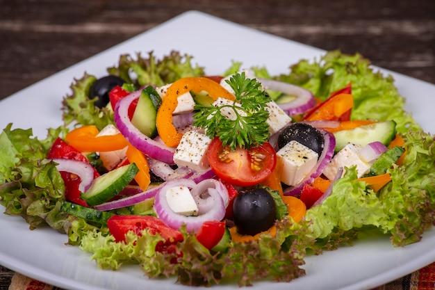 Griechischer gemüsesalat des frischen gemüses in der weißen platte auf holztisch, nah oben Premium Fotos