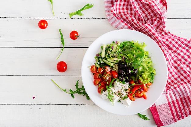 Griechischer salat aus frischen gurken, tomaten, paprika, salat, zwiebeln, feta-käse und schwarzen oliven Premium Fotos