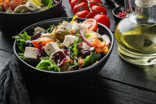 Griechischer salat mit frischem gemüse, feta-käse und oliven kalamati, auf schwarzem holztisch Premium Fotos