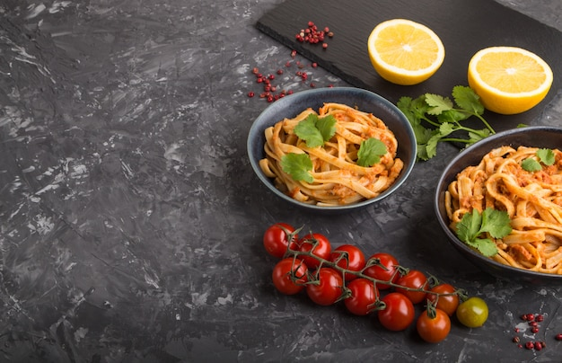 Grießnudeln mit tomaten-pesto-sauce, orangen und kräutern. seitenansicht, exemplar. Premium Fotos