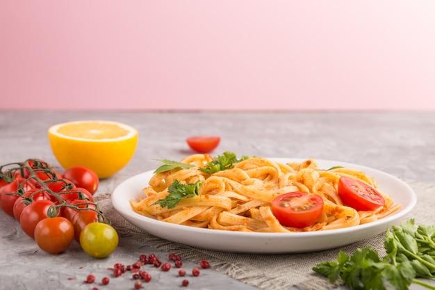 Grießnudeln mit tomaten-pesto-sauce, orangen und kräutern. seitenansicht Premium Fotos