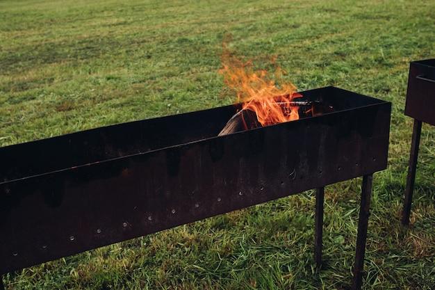 Grill mit flammendem feuer und brennholz Premium Fotos