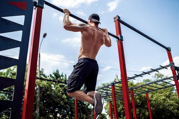 Grober athletischer mann, der klimmzugübungen auf einer querlatte macht. Premium Fotos
