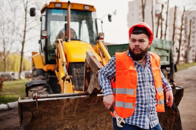 Grober bartarbeitskraftmann-klagenbauarbeiter im orange sturzhelm der sicherheit, gegen traktor mit dem justierbaren schlüssel zur hand. Premium Fotos