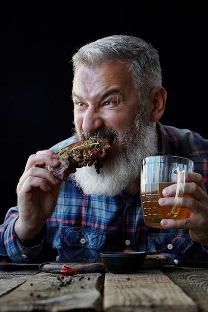 Grober grauhaariger erwachsener mann mit bart isst senfsteak und trinkt bier, lädt zu einer mahlzeit, konzept eines feiertags, festival, oktoberfest ein Premium Fotos