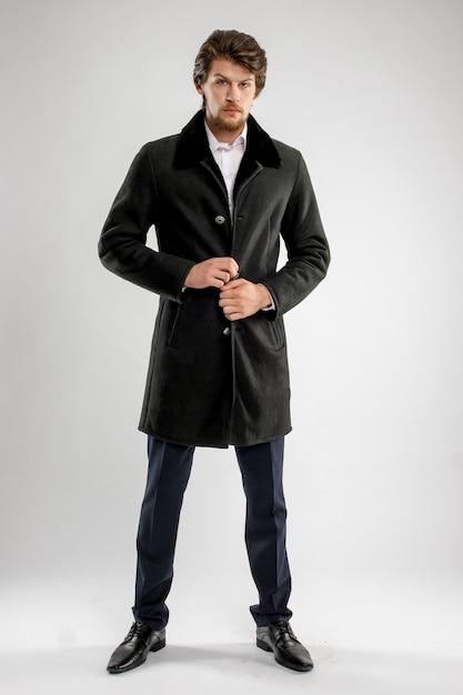 Grober hübscher unrasierter mann mit bart und schnurrbart im schaffellmantel mit pelzkragen Premium Fotos