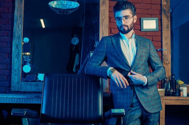 Grober mann im eleganten anzug und in den gläsern im friseursalon Premium Fotos