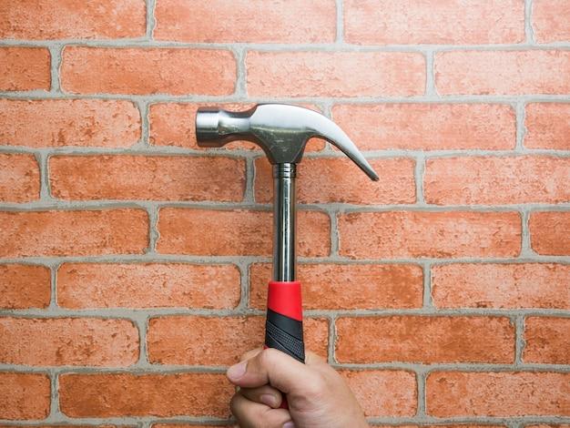 Großaufnahme der hand eines mannes, die hammer mit backsteinmauer hält. reparatur und wartung. Premium Fotos