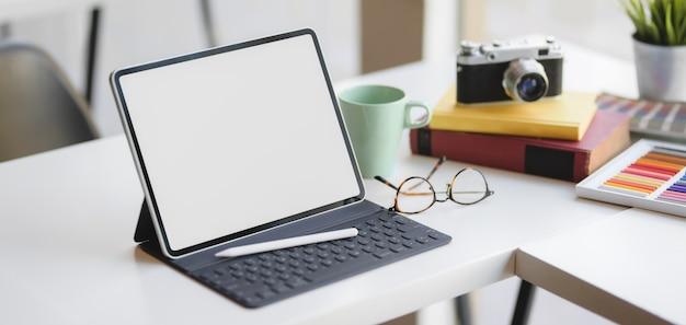 Großaufnahme des bequemen designerarbeitsplatzes mit digitaler tablette und büroartikel des leeren bildschirms Premium Fotos