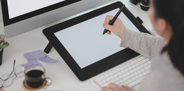 Großaufnahme des jungen weiblichen designers, der an ihrem projekt bei der anwendung der tablette arbeitet Premium Fotos